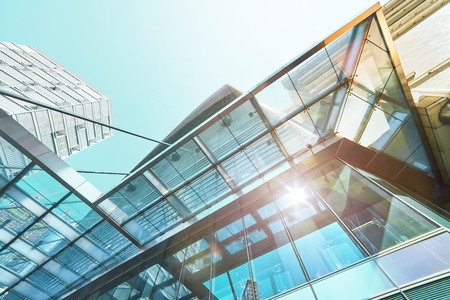 Abstract low angle view of contemporary glass structure skyscraper against clear sky . Stock Photo