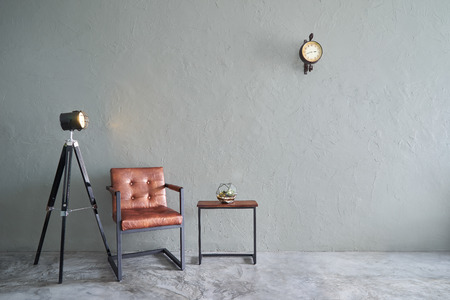 Modern living room with brown iron chair , clock ,tea table,cactus  and lamp stand. cement floor and concrete wall ,Interior design with Loft style .