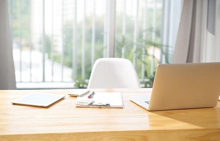 Oficina vacía del espacio de trabajo con la computadora portátil, la tableta digital, el smartphone, la nota y la pluma, escena de la mañana.
