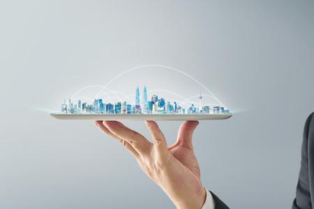 Mano del camarero que sostiene una tableta digital vacía con concepto elegante del paisaje urbano y de la conexión de red. Aislado sobre fondo gris