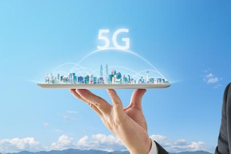 Mano de camarero sosteniendo una tableta digital vacía con paisaje urbano inteligente y el concepto de conexión de red 5G. Foto de archivo