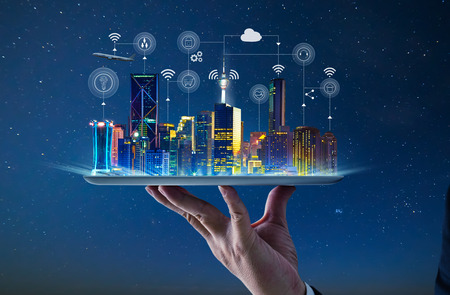 Waiter hand holding an empty digital tablet with Smart city with smart services and icons, internet of things, networks and augmented reality concept , night scene . 스톡 콘텐츠