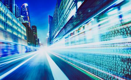 La via della città con i numeri di codice binario su moto ha offuscato la strada asfaltata, la velocità e concetto più veloce di informazioni di tecnologia della matrice digitale.