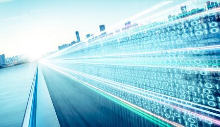 Le survol de l'autoroute avec des numéros de code binaire sur la route de bitume en mouvement floue, la vitesse et un concept d'information sur la technologie de la matrice numérique plus rapide.