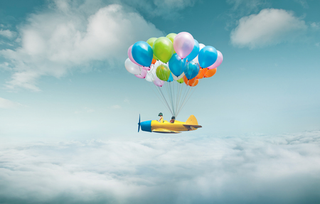 Happy sister enjoy with fantasy plane fly  and floating in sky with bunch of colorful balloons . Banque d'images