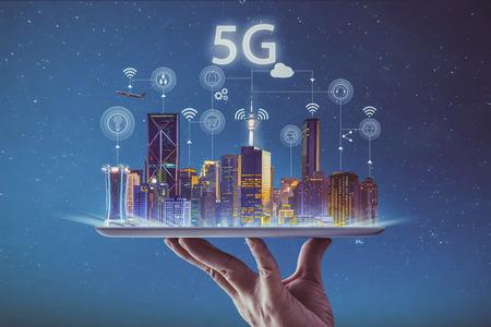 Camarero mano sosteniendo una tableta digital vacía con ciudad inteligente y sistemas inalámbricos de red 5G e internet de las cosas.