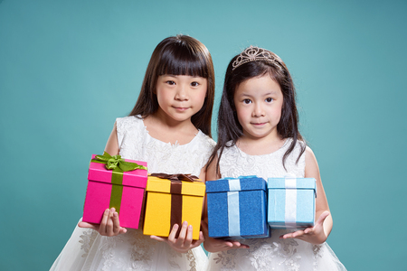 Portrait of two little asian beautiful girl holding four present box on vintage blue background. Фото со стока