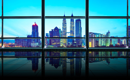 Modern empty and clean office interior with glass windows , Kuala Lumpur city skyline background , early morning scene .