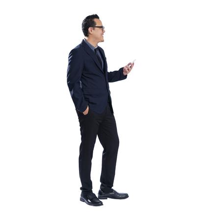 Full length portrait of smile asian businessman holding handphone . Isolated on white background .