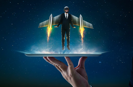Waiter hand holding an empty digital tablet with Businessman wear a rocket suit to lift , Business success concept . Imagens - 93255175