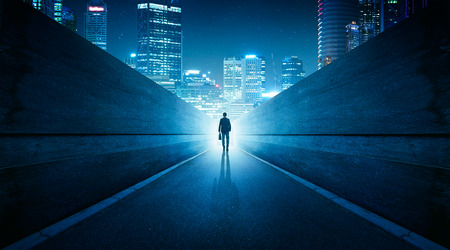 Ambitions concept with businessman walking from alley to modern city . Night scene .