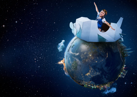 Little cute girl playing with a cardboard airplane with Earth planet background .Childhood dream imagination concept . .Extremely detailed image