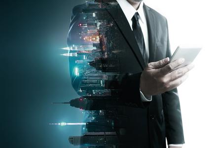 Imagen abstracta de doble exposición del hombre de negocios que usa la mezcla de teléfonos inteligentes móviles con fondo creativo de la ciudad de flip night. Siempre mantente conectado concepto.