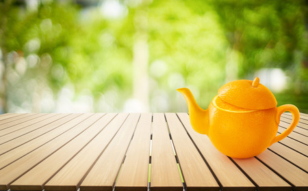 Teapot of Orange fruit on wooden table with out of focus green park background .Concept of  juice with fresh fruits .