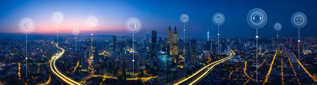 Vue aérienne panoramique dans les toits du paysage urbain avec des services intelligents et des icônes, l'Internet des objets, les réseaux et le concept de réalité augmentée, scène du lever du soleil tôt le matin.