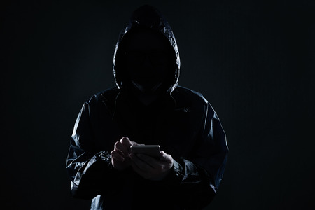Unrecognizable hacker using mobile phone portrait, mobile phone security and technology crime concept . Stock Photo