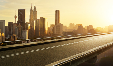 Empty asphalt flyover  road with modern cityscape skyline , sunrise scene .