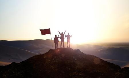 Silueta del equipo empresarial en la cima de una montaña. Concepto de liderazgo y éxito empresarial.