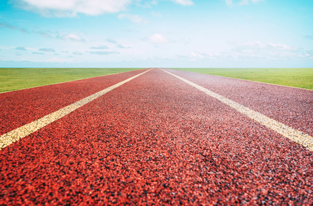 Red running track with sky background . 写真素材
