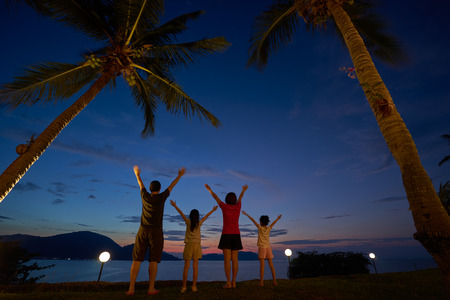 The family raised their hands and cheered to enjoy the seaside at dusk Imagens