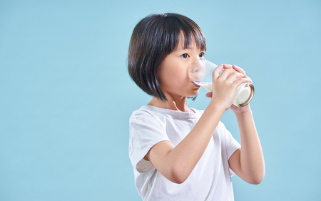 Cute smart asian little girl drinking milk on blue background Stockfoto