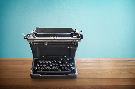 Old vintage retro black Typewriter on wood table with mint blue background
