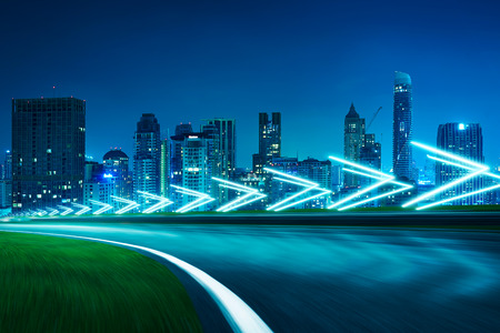 Motion blurred racetrack,cityscape night scene cold mood. with arrow light Effects. Imagens