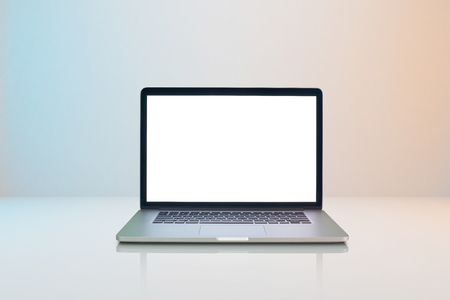 Laptop with white blank screen on milky white background with slightly blue and orange lighting . Imagens