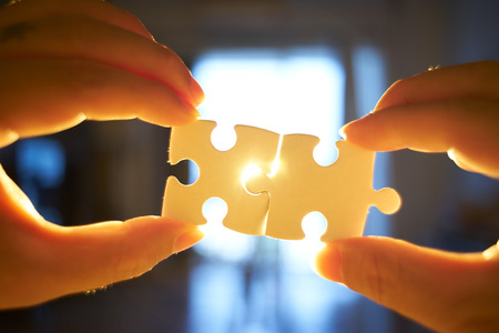 Young businessman trying to connect couple puzzle piece with sun flare and blur background,symbol of association and connection. business strategy. Standard-Bild - 118982474
