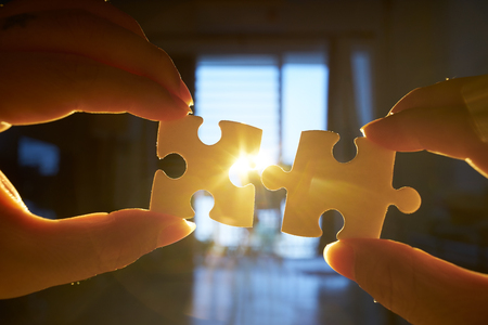 Young businessman trying to connect couple puzzle piece with sun flare and blur background,symbol of association and connection. business strategy. Banco de Imagens