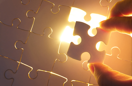 Young businessman trying to put back missing jigsaw puzzle piece with light golden glow effect . Business strategy concept . Standard-Bild - 118982479