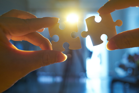 Young businessman trying to connect couple puzzle piece with sun flare and blur background,symbol of association and connection. business strategy. Standard-Bild - 118982481