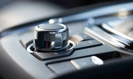 Closeup of a modern car interior with media and navigation control buttons