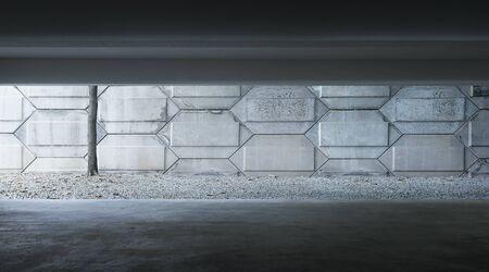 Parking intérieur vide en sous-sol avec façade en ciment.