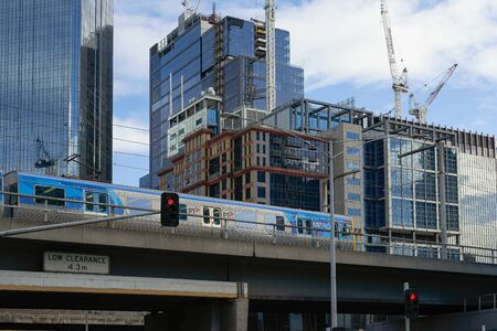 MELBOURNE, AUSTRALIA - OCTOBER 26,2019 : PT Metro Train running through in front of commercial building in CBD , Melbourne city .
