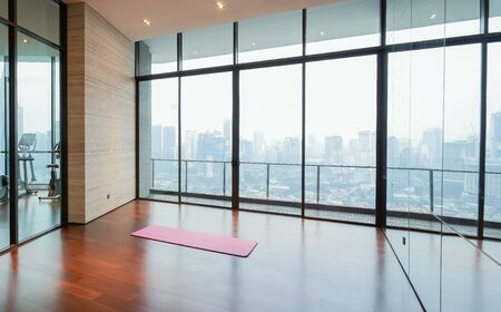 Unrolled yoga mat on wooden floor in fitness center with cityscape  scene