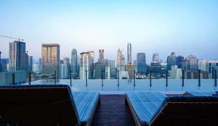 Relaxing chair on rooftop swimming pool with beautiful morning cityscape view. Imagens