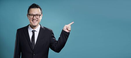 Businessman in suit smile and finger point to the right . Horizontal format