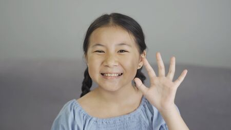 Cute asian little girl smiling and waving hand looking at camera at home