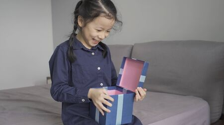 Asian little girl very happy and excited when receives a gift box, New year, Merry Christmas or Birthday present gift concept