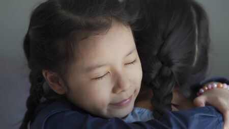Beautiful and adopted asian little girl hugging, sweet moment with love