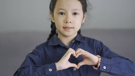 Beautiful little asian girl making a heart shape hand gesture, love and friendship forever concept