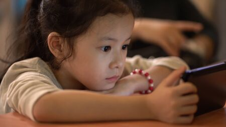 Asian little girl focus watching smartphone Imagens