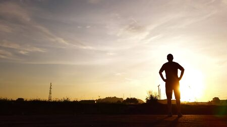 Silhouette of young man relaxing in summer sunrise sky outdoor. Lifestyle freedom concept . Imagens
