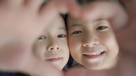 Happy sister make heart shape hand gesture, love and friendship forever concept,close up angle