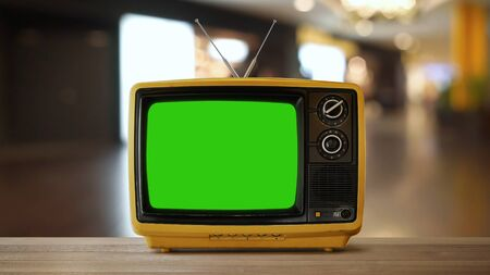Yellow orange color old vintage retro Television on wood table with green screen . Imagens