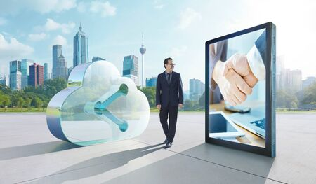 Young asian businessman walking beside on transparent glass symbol of cloud storage and big digital billboard with shake handsimage. Successful case of digital cloud network service business concept.