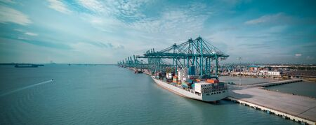 Logistics container cargo ship with working crane bridge in import export terminal port, international logistics transport industry background, Panorama arial view.