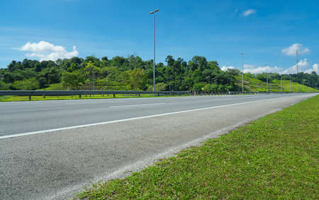 Perspective view of empty highway road with railing,green hill,blue sky and light poles