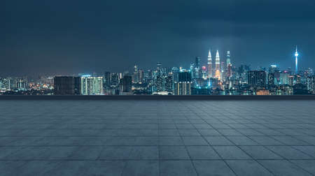 Empty concrete tiles floor with city skyline background. Night scene 免版税图像